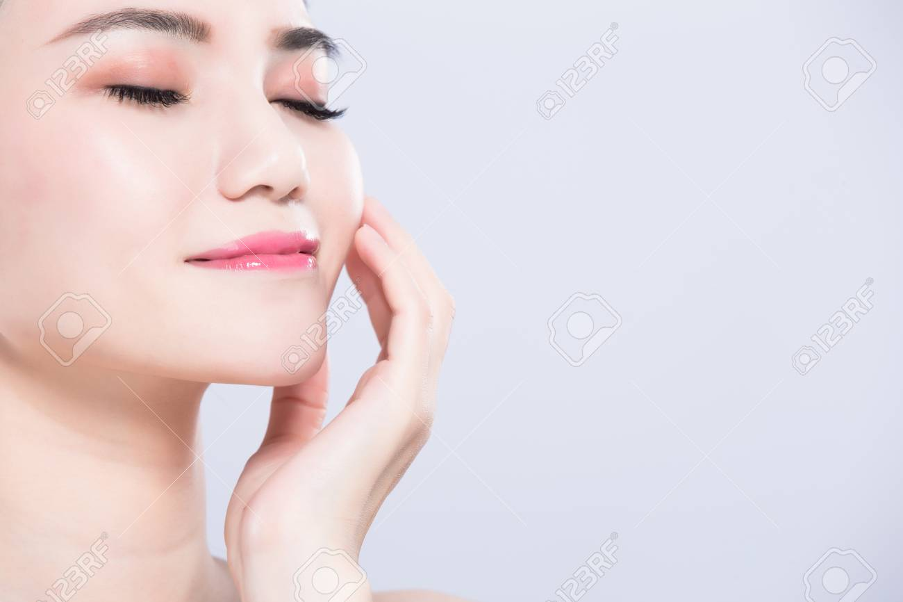 97314076-woman-close-eyes-and-touch-face-with-beauty-skin-care-concept-on-the-gray-background